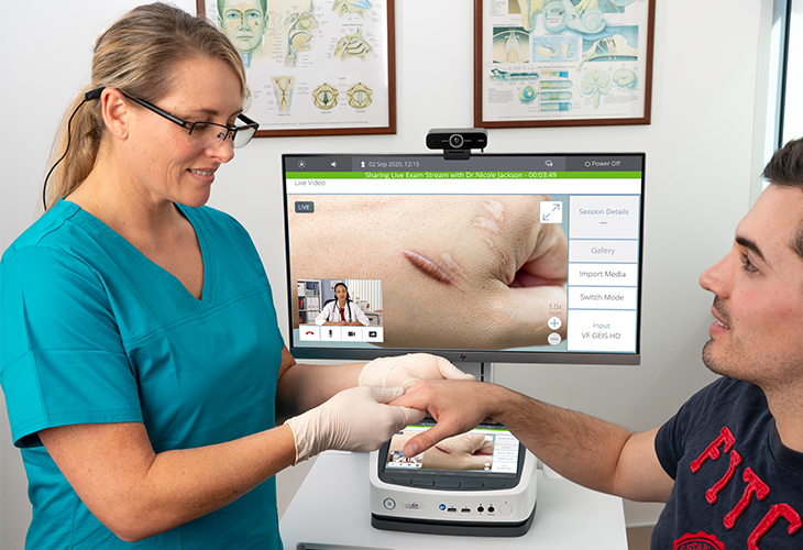 Nurse wearing video glasses inspecting male patient hand scars and wound